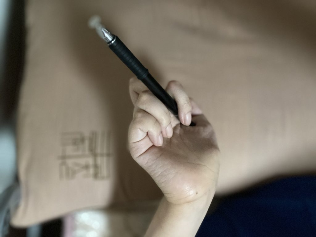 右手の指にペンをはさんだ写真